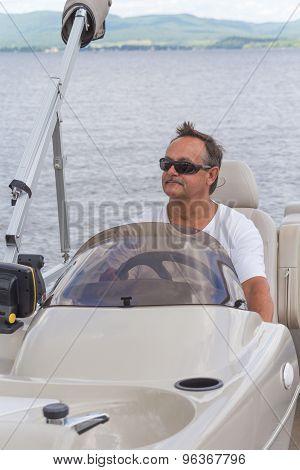 mature men driving a pontoon boat on a lake