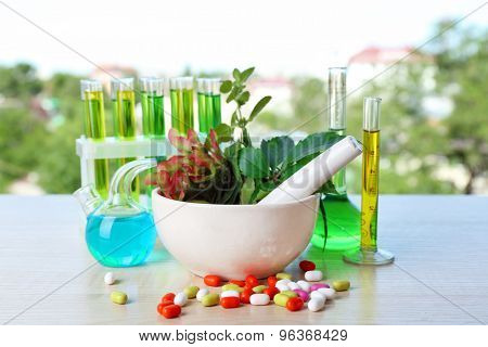 Herbs in mortar, test tubes and pills,  on table, on bright background