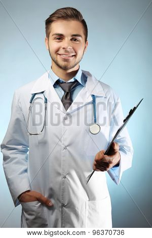Male doctor with folder on blue background