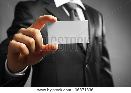 Handsome businessman holding business card close up
