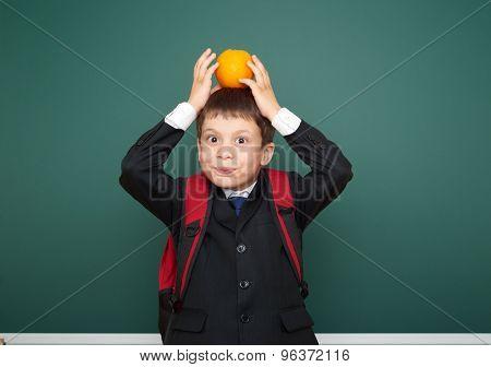 Schoolboy with orange near the school board