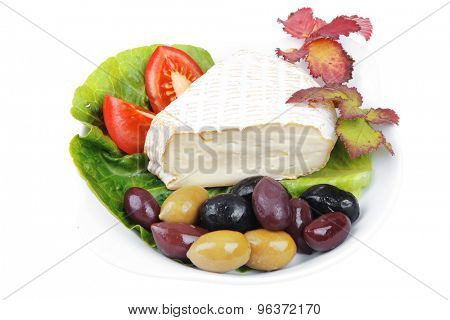 aged brie cheese on salad in white dish with olives and tomato isolated over white background