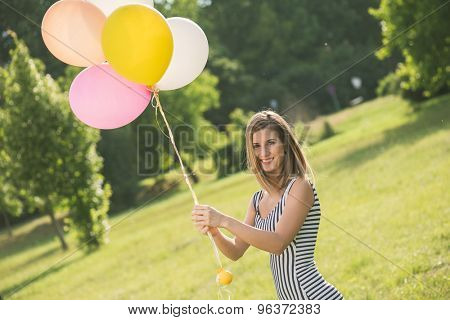 young beautiful girl with baloons posing outdoor