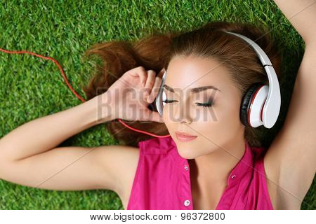 Young Beautiful Girl Laying On The Grass In Park Listening To Music