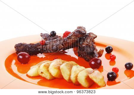grilled beef meat with berries fried potatoes and cherry under sweet honey sauce on orange plate isolated over white background