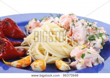 fresh rose wild salmon baked in cream cheese sauce with italian pasta and red hot pepper on blue plate isolated over white background