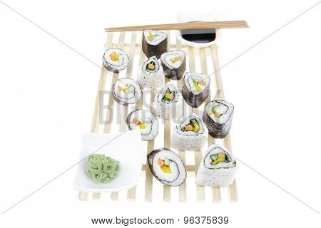 Maki Roll with Deep Fried Vegetables inside . on wooden grid . isolated over white background . Japanese Cuisine