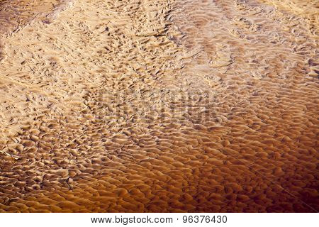 Wavy sand texture patterns on the bottom of the river in red