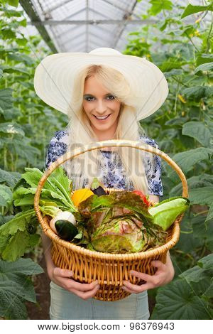 Attractive blond woman with a basket of vegetables