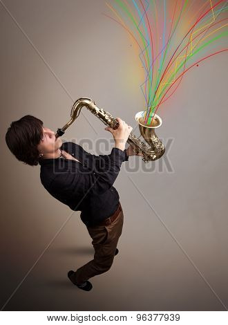 Attractive young musician playing on saxophone while colorful abstract lines exploding