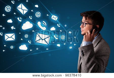 Young man staning and making phone call with message icons