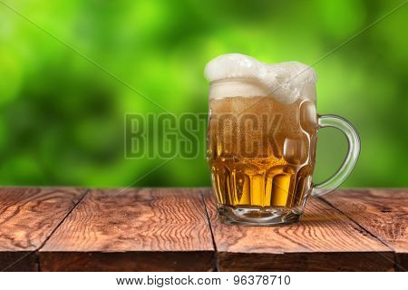 Beer in glass on wooden table with blurred green summer leaves on natural background with bokeh
