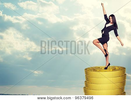 Smiling businesswoman standing on coins stack