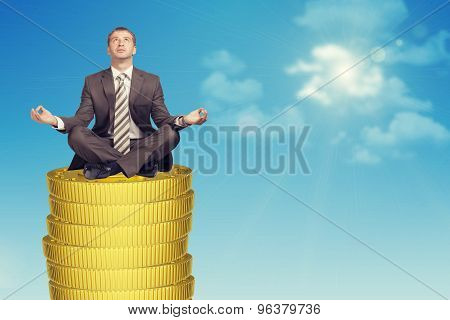 Businessmanin in lotus posture on coins stack
