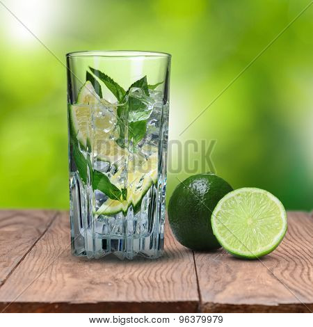 mohito cocktail with lime on wooden table against green natural background