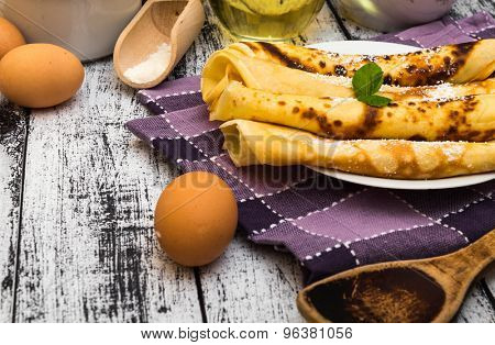 pancakes and ingredients on a wooden background