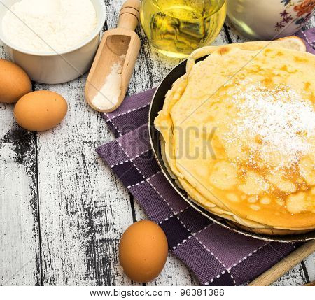 stack of pancakes and ingredients on a wooden background