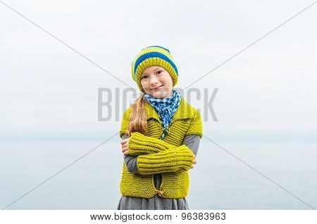 Outdoor portrait of a cute little girl dressed in warm pistache color knitwear