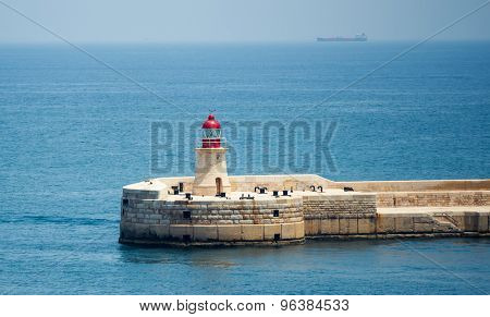 lighthouse in Valletta port of Malta on misty sea background with a ship