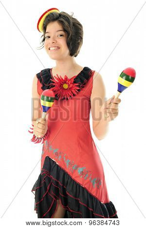 An attractive young teen happily wearing a red and black Mexican dress, a tiny sombrero and shaking colorful maracas.  On a white background.