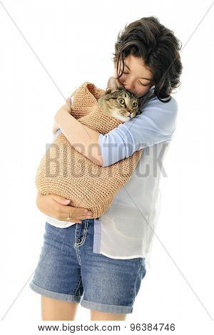 An attractive young teen loving on her pet Tabby cat.  Focus on girl.  On a white background.