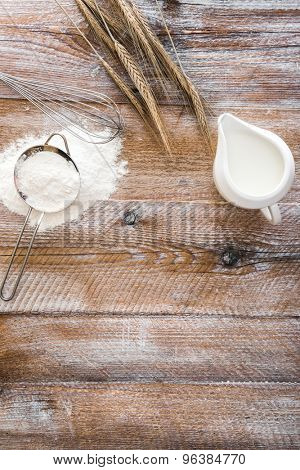 Flour sieve, wheat ears and jug on a wooden table