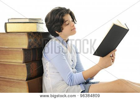An attractive young teen reading one book as she sits leaned against a stack of huge old books with a couple more on top.  On a white background.