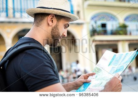 Tourist consulting a city guide searching locations in the street