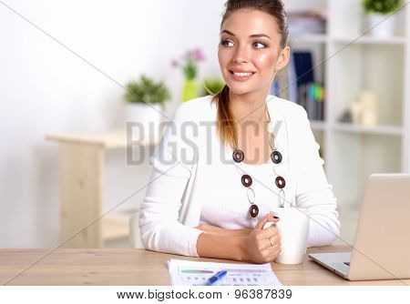 Cute businesswoman holding newspaper sitting at her desk in office .