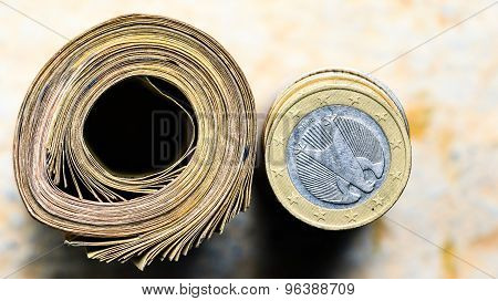 Savings ~ Roll of currency note and stacked coins kept on a plain background