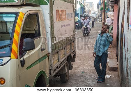MUMBAI, INDIA - 12 JANUARY 2015: Indian man stands next to truck in Dharavi slum and talks on cellphone. Dharavi is one of the largest slums in the world.