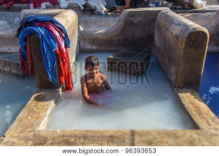 MUMBAI, INDIA - 10 JANUARY 2015: Indian child bathes in traditional laundromat pool in Dhobi Ghat. A well known open air laundromat in Mumbai.