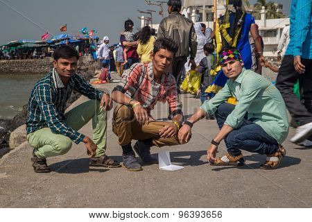MUMBAI, INDIA - 09 JANUARY 2015: Three Indian boys crouch next to sea while people pass by them towards Haji Ali Dargah temple. A mosque and tomb located on an islet.