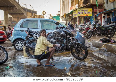 MUMBAI, INDIA - 16 JANUARY 2015: Young Indian boy hand washes motorbike in dirty parking space. Bike is soaked in soap.