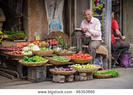 MUMBAI, INDIA - 17 JANUARY 2015: Elderly Indian businessman waits for customers in front of grocery store in market street.