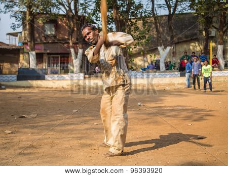 MUMBAI, INDIA - 16 JANUARY 2015: Adult Indian man hits ball with wooden cricket bat on school playground.