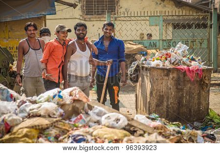 MUMBAI, INDIA - 16 JANUARY 2015: Five adult garbage men pile up garbage on slum street before throwing into garbage truck.