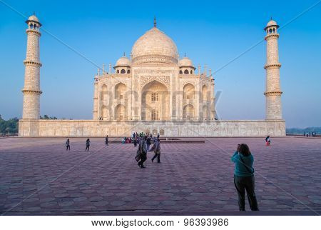 AGRA, INDIA - 28 FEBRUARY 2015: View of Taj Mahal from East side. Woman photographs Taj.