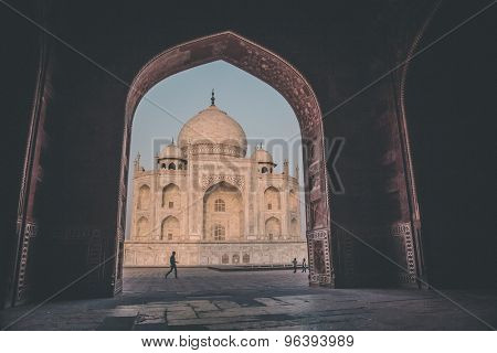 AGRA, INDIA - 28 FEBRUARY 2015: View of Taj Mahal from inside Mihman Khana with people passing by. East side of Taj. Post-processed with grain, texture and colour effect.