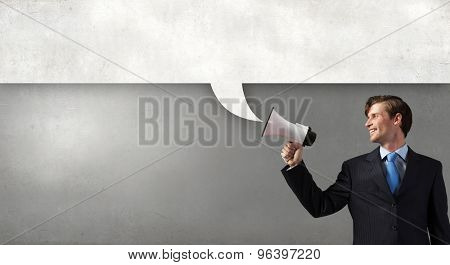 Young businessman speaking in megaphone and speech bubble for text
