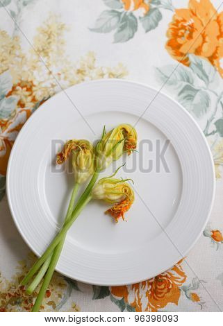 Fresh zucchini flowers on plate