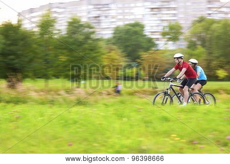 Portrait Of Young Sportive Caucasian Couple Outdoors Having Time Together And Riding Bicycles