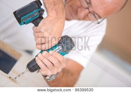 Carpenter using a cordless drill