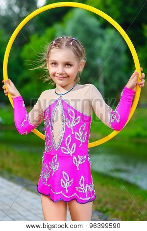 fitness, sport, people and healthcare concept - little sporty girl exercising with hula hoop over pa