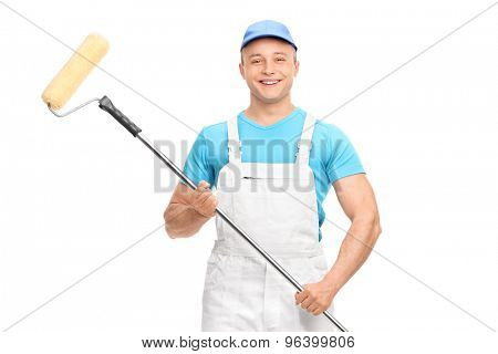 Young male house painter in a white overalls holding a paint roller and looking at the camera isolated on white background