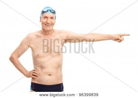 Senior man in black swim trunks pointing with his hand towards right and looking at the camera isolated on white background