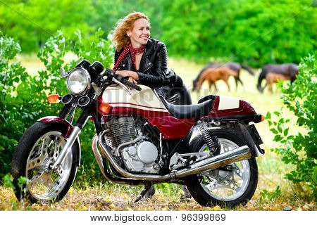 Biker girl in leather jacket on a motorcycle against the background of horses