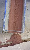 image of concrete pouring  - Pouring concrete colored red for filling fiber optic cables microtrench - JPG