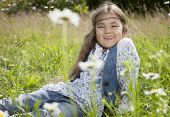 picture of hippy  - Beautiful little girl in hippie style sitting in the field smiling at the camera - JPG
