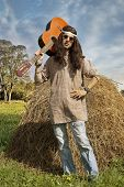 image of hippy  - Portrait of long haired middle aged hippie man with a guitar